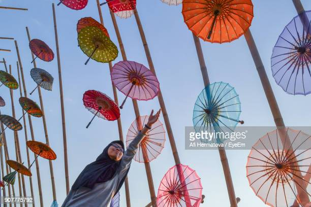 low angle view of woman by umbrellas hanging against sky - surakarta stock photos and pictures