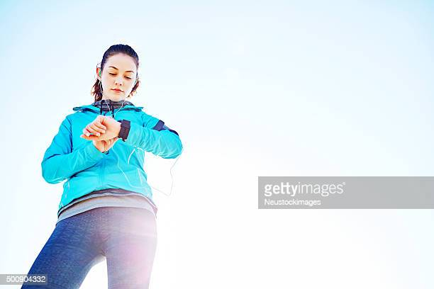 Low angle view of woman checking fit watch after run
