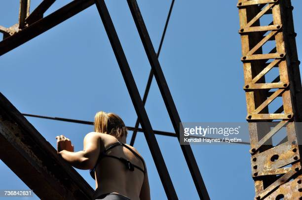 Low Angle View Of Woman Climbing On Bridge