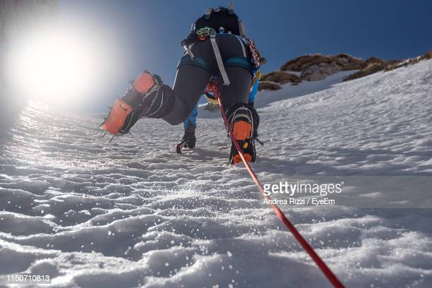low angle view of woman climbing snow covered mountain - andrea rizzi stockfoto's en -beelden