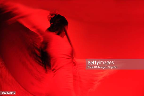 Low Angle View Of Woman Dancing Against Red Background