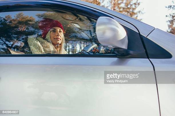 Low angle view of woman driving car during winter