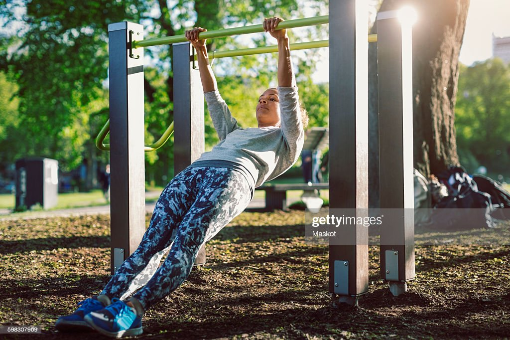 Low angle view of woman exercising on railing at park : ストックフォト