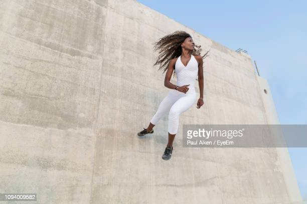 Low Angle View Of Woman Exercising On Wall