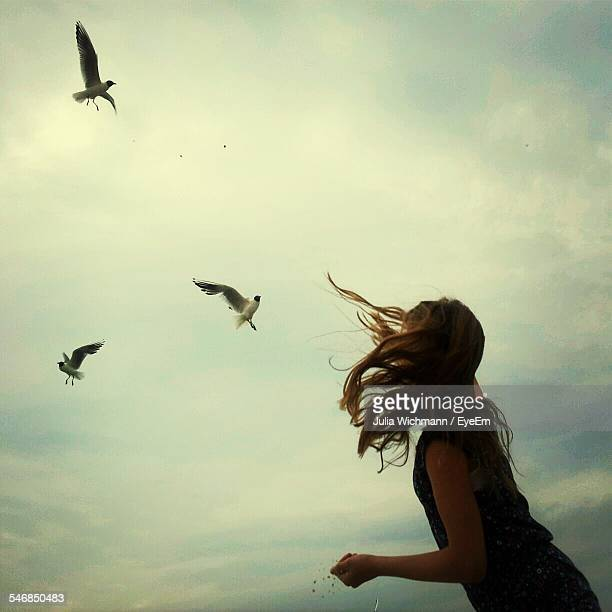 Low Angle View Of Woman Feeding Birds Against Sky