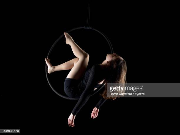 Low Angle View Of Woman Hanging On Ring Against Black Background