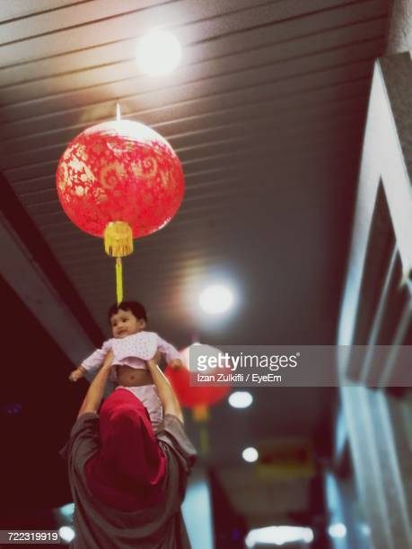Low Angle View Of Woman Holding Aloft Baby Below Red Chinese Lantern