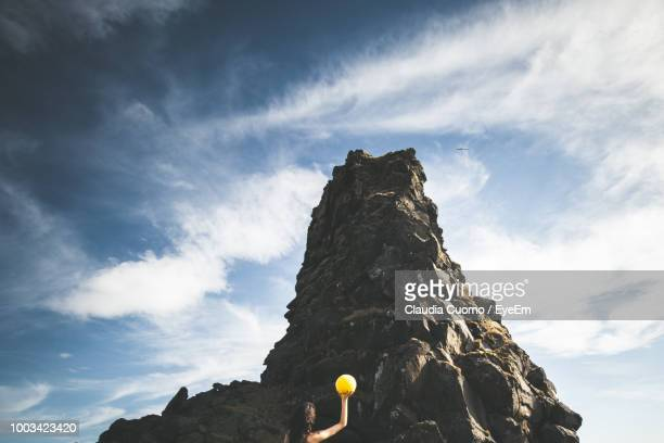 low angle view of woman holding ball by rock formation against sky - cuomo stock pictures, royalty-free photos & images