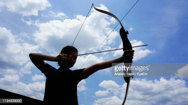 low angle view of woman holding bow and arrow while standing against sky - arco y flecha fotografías e imágenes de stock