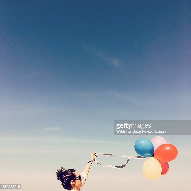 Low Angle View Of Woman Holding Helium Balloons Against Sky