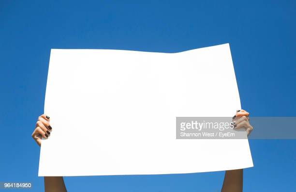low angle view of woman holding placard against blue sky - demonstrant stock-fotos und bilder