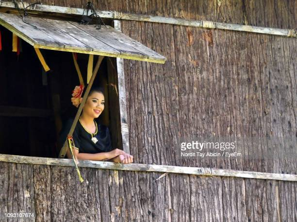 low angle view of woman in house seen through window - sarawak state stock pictures, royalty-free photos & images