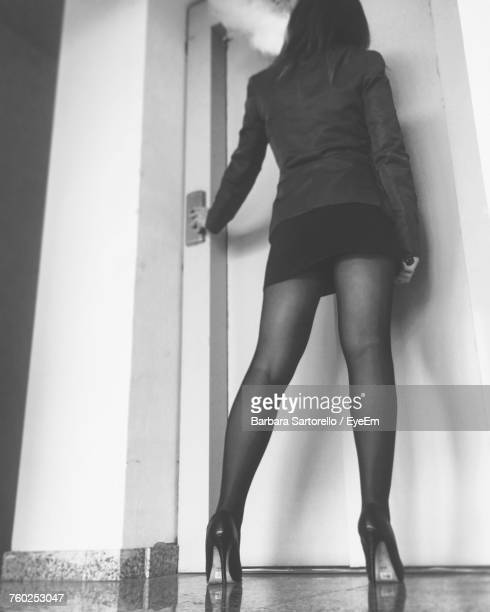 low angle view of woman in mini skirt standing at entrance door - high heels short skirts stock pictures, royalty-free photos & images