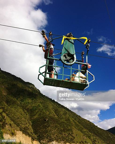 Low Angle View Of Woman In Overhead Cable Car Against Sky