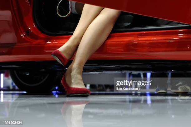 Low angle view of woman in red high heels sitting in car, legs only