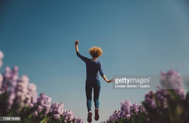 low angle view of woman jumping against clear sky - bortes stock-fotos und bilder