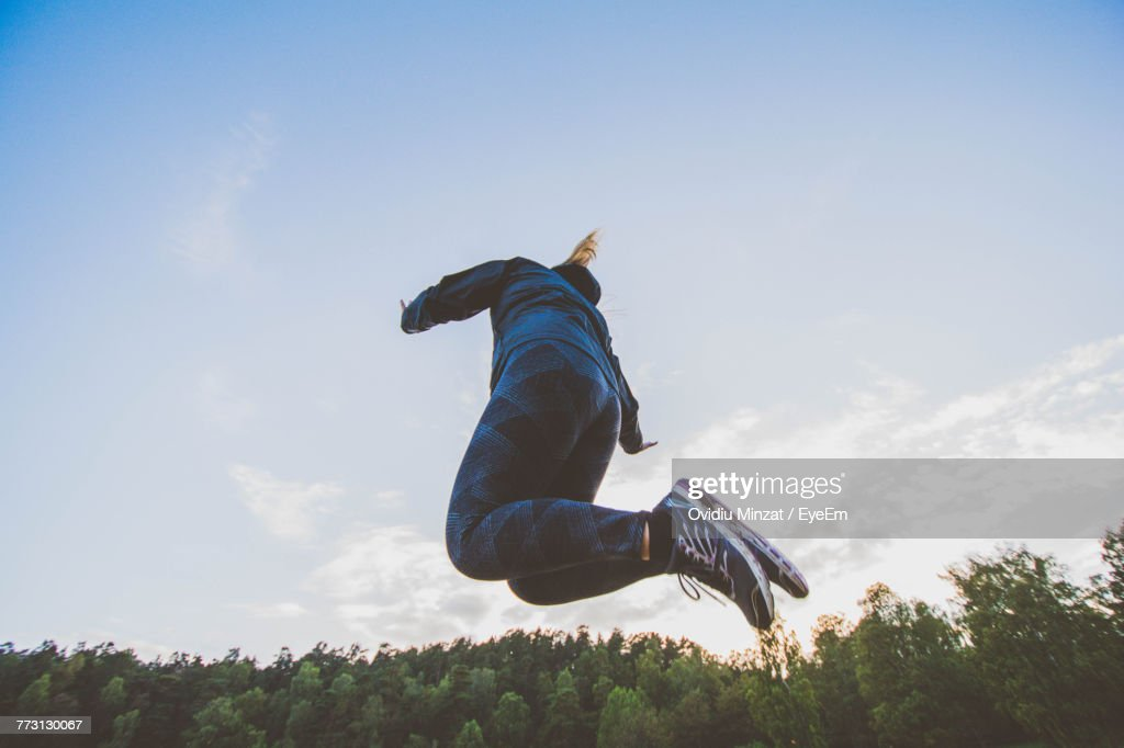 Low Angle View Of Woman Jumping Against Sky : Stock Photo