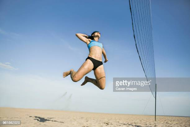 low angle view of woman jumping while playing volleyball at beach - strandvolleyball spielerin stock-fotos und bilder