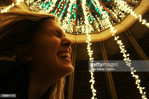Low Angle View Of Woman Laughing Against Illuminated Ceiling