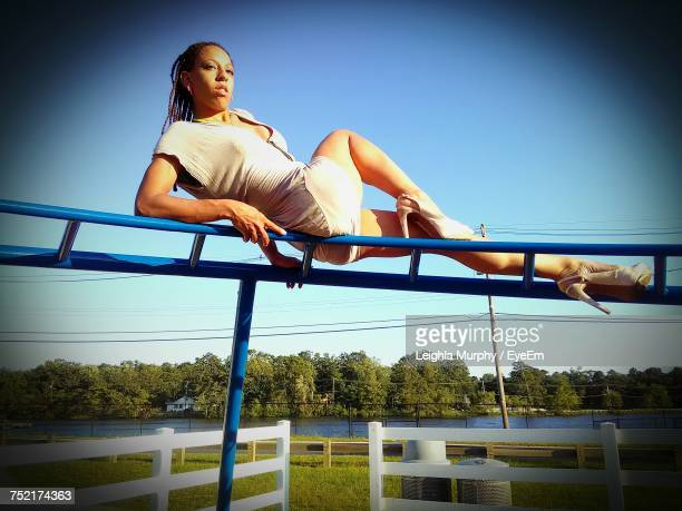 low angle view of woman leaning on monkey bars at park - monkey shoes stock photos and pictures