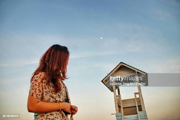 Low Angle View Of Woman Looking At Lifeguard House Against Sky