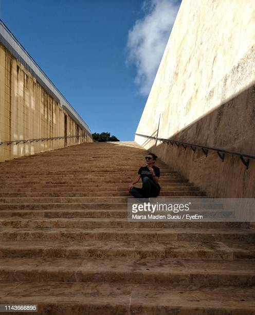 low angle view of woman looking away sitting on staircase - madlen stock-fotos und bilder