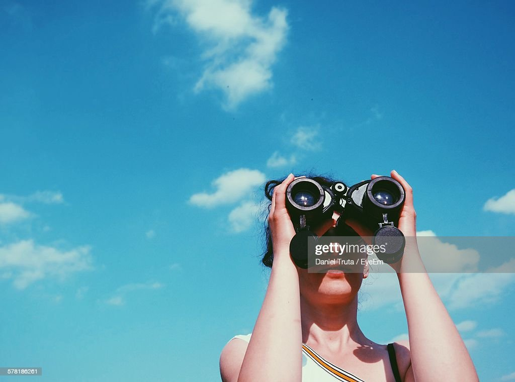 Low Angle View Of Woman Looking Through Binoculars Against Sky : Stock-Foto