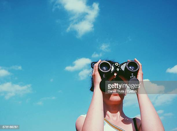 Low Angle View Of Woman Looking Through Binoculars Against Sky