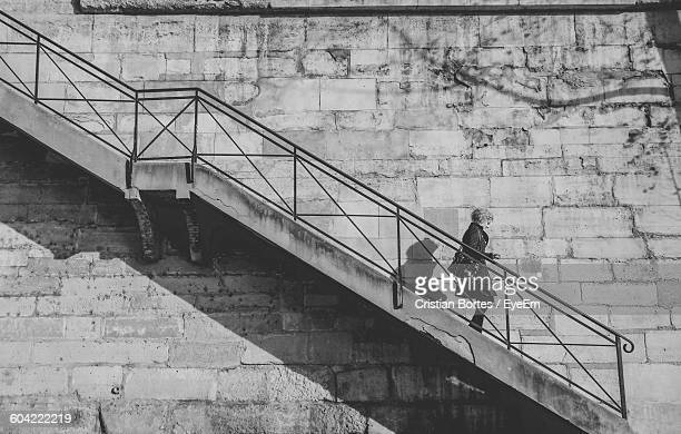 low angle view of woman moving down on steps against wall - bortes stock-fotos und bilder