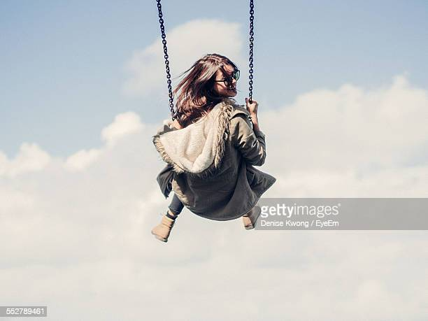 low angle view of woman on swing against cloudy sky - ブランコ ストックフォトと画像