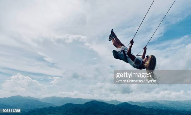 low angle view of woman on swing against sky - ブランコ ストックフォトと画像