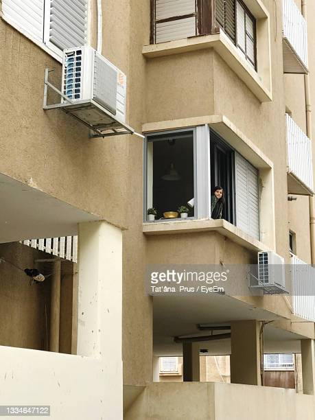 low angle view of woman peeking from building window - netanya stock pictures, royalty-free photos & images