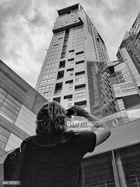 Low Angle View Of Woman Photographing To Modern Building