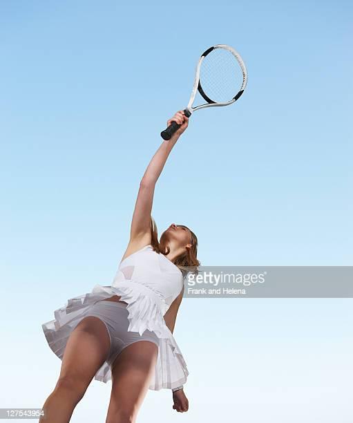 Vue depuis un angle bas de Femme jouant au tennis