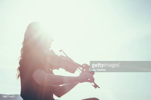 low angle view of woman playing violin against sky on sunny day - classical music stock pictures, royalty-free photos & images
