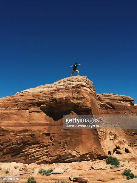Low Angle View Of Woman Practicing Yoga On Rock Formation Against Clear Blue Sky