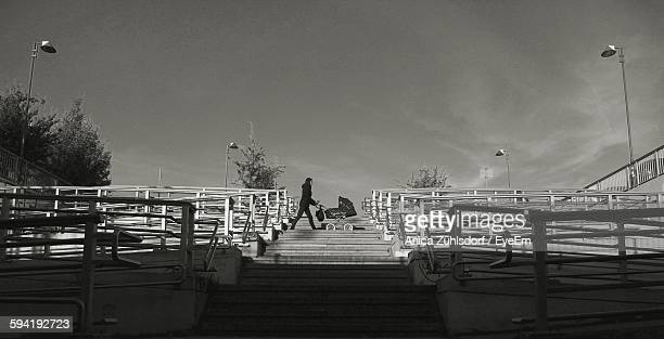 Low Angle View Of Woman Pushing Baby Carriage On Steps Against Sky