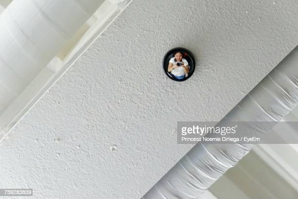 Low Angle View Of Woman Reflecting On Recessed Light On Ceiling