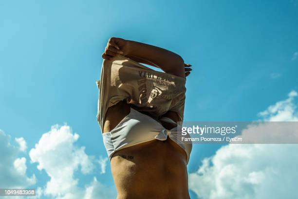 low angle view of woman removing top against sky - remove clothes from stock pictures, royalty-free photos & images