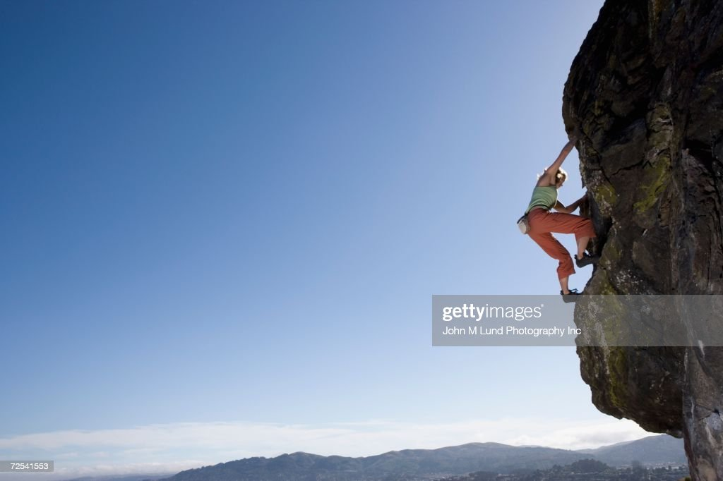 Low angle view of woman rock climbing : Photo