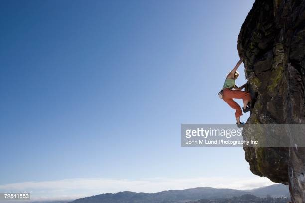 Low angle view of woman rock climbing