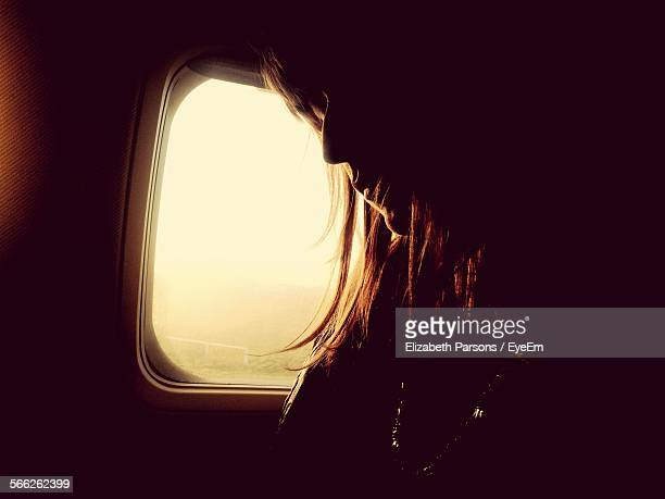 Low Angle View Of Woman Sitting By Airplane Window