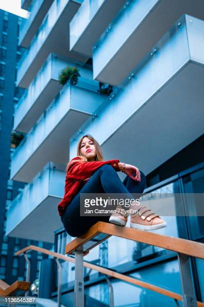 low angle view of woman sitting on railing against building in city - vista de ángulo bajo fotografías e imágenes de stock