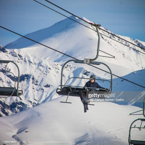 low angle view of woman sitting on ski lift against snowcapped mountains - ski lift stock pictures, royalty-free photos & images
