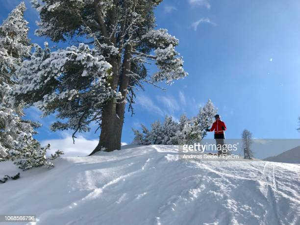 low angle view of woman skiing on mountain against sky - reality fernsehen stock pictures, royalty-free photos & images