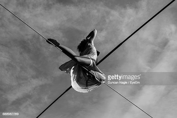 Low Angle View Of Woman Slacklining Against Sky