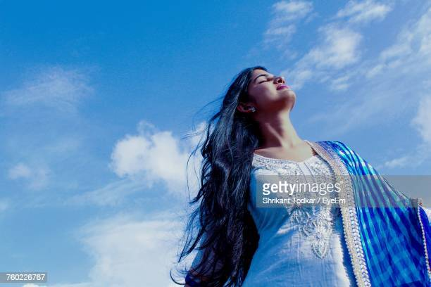 low angle view of woman standing against blue sky - salwar kameez stock pictures, royalty-free photos & images