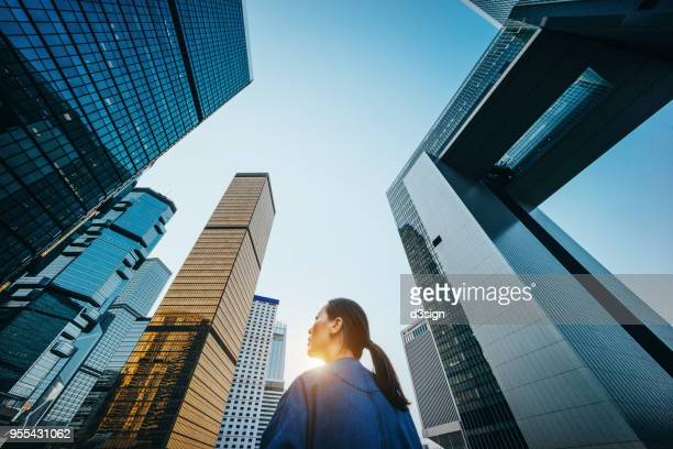 low angle view of woman standing against modern skyscrapers and blue sky in city at sunrise - low angle view stock pictures, royalty-free photos & images