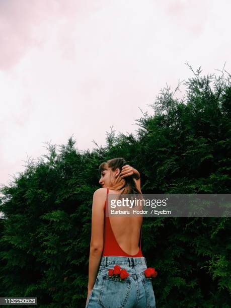 low angle view of woman standing against plants - backless stock pictures, royalty-free photos & images