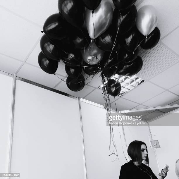 Low Angle View Of Woman Standing By Helium Balloons In Room